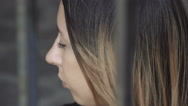 sad young woman trapped behind bars Stock Footage