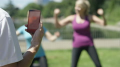 4K Healthy & fit mature ladies working out with personal trainer in the park Stock Footage