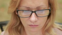Woman with glasses reading a book. close-up. reflected in the lenses of the book Stock Footage