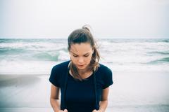 Attractive female athlete with a skipping rope on the beach in cold weather Stock Photos