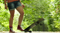 Girl raises a leg a skateboard in green park. Slow motion Stock Footage