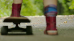 teenager  girl  legs with  skateboard in green park move away. Slow motion Stock Footage