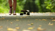 teenager  girl  legs with  skateboard in green park approach. Slow motion Stock Footage