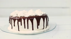 White cake covered with chocolate and cream Stock Footage