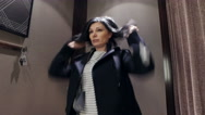 Young woman trying on a coat in the dressing shop Stock Footage