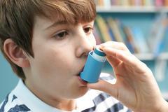 Boy Using Inhaler To Treat Asthma Attack Stock Photos