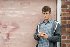 Teenage Boy Texting On Mobile Phone In Urban Setting Stock Photos
