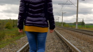 Woman walking on railroad tracks Stock Footage