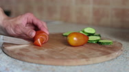 Image of male hand with knife cutting cucumbers on wooden board Stock Footage