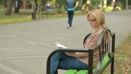 Blonde Woman Reading Book on Brench in Autumn Park. drinking hot coffee or tea Stock Footage