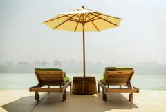 Infinity pool with parasol and sun beds at seaside Stock Photos