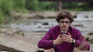 Handsome man using smartphone outdoors with river on background Stock Footage