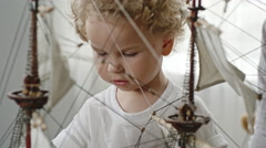 Little Toddler Playing with Ship Model Stock Footage