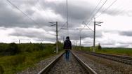 Woman walking on railroad tracks Stock Footage