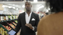 4K Salesman talking to supermarket buyer, holding tablet & negotiating a deal Stock Footage
