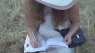 Girl with pen writing on notebook on grass outside Stock Footage