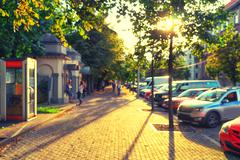 Blurred alley with trees in the city of Riga in late August Stock Photos