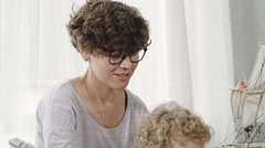 Curly Mother and Son Playing with Ship Model Stock Footage