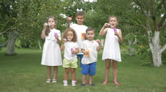 Little kids blow bubbles in the park Stock Footage