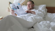 Man in bed reading the morning newspaper Stock Footage