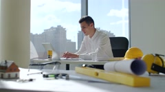 Young brunette architect sits by the table near a large window in white office Stock Footage