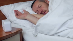 Man sleeping in bed and wakes up from the alarm clock Stock Footage