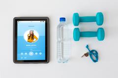 Tablet pc, dumbbells, whistle and water bottle Stock Photos