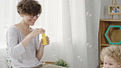 Smiling Mother Blowing Soap Bubbles Stock Footage