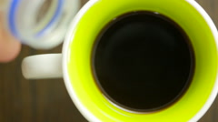 Pouring milk into a mug of coffee. view from above Stock Footage