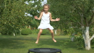 Little girl jumping on the trampoline in the garden Stock Footage