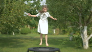 The cute girl jumping on the trampoline in the garden Stock Footage