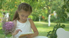 The girl playing on the tablet in the garden Stock Footage