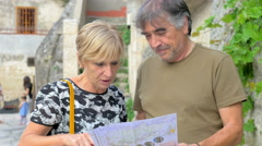 Two middle-aged tourists consult the map and decide where to go Stock Footage