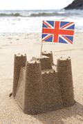 Sandcastle On Beach With Union Jack Flag Stock Photos