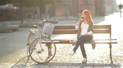 Cute redheaded girl is resting, sitting on a bench in the city. She postponed Stock Footage