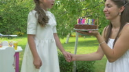 The girl blows out the candles on the cake Stock Footage