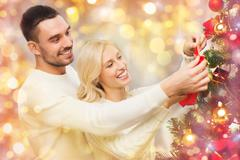 Happy couple decorating christmas tree at home Stock Photos