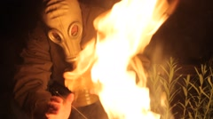 Person in a gas mask is heated by the fire Stock Footage