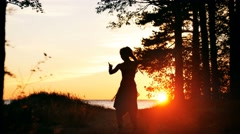 Silhouette of young woman dancing in sunset Stock Footage