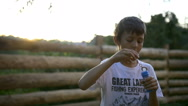 Boy inflates the bubble that burst at sunset Stock Footage
