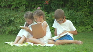 The children sitting on the grass in the garden Stock Footage