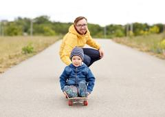 Happy father and little son riding on skateboard Stock Photos
