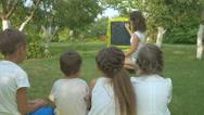 The teacher teaches the children in the garden Stock Footage