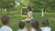 The woman teaches the kids in the garden Stock Footage