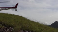 Camera pans over left to helicopter sitting on hilltop preparing for takeoff Stock Footage