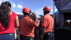 Men wearing matching red shirts and helmets standing amist crowd Stock Footage