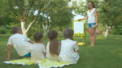 The woman teaching the children in the garden Stock Footage