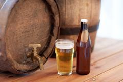 Close up of old beer barrel, glass and bottle Stock Photos