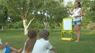 Young woman teaches the children in the garden Stock Footage