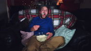 4k Authentic Shot of a Funny Man Watching Horror Movie with Popcorn  Stock Footage